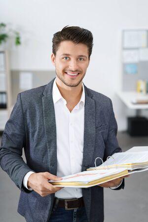 carpeta: joven hombre de negocios dinámico de pie en la oficina que sostiene una carpeta Foto de archivo