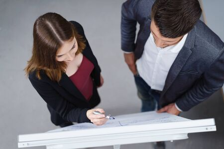 standing together: Successful young business team standing alongside a flip chart brainstorming a problem or planning their strategy, overhead view of a young man and woman Stock Photo