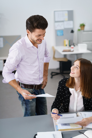 officeworker: two young office-worker talking inside the workplace