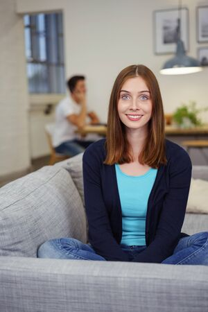 jaunty: Attractive young woman relaxing at home sitting cross-egged on a sofa in her living room looking at the camera with a lively friendly smile as her husband works at a table in the background