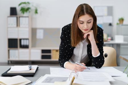 Attraktive junge Bürofrau, die an der Geschäftspapiere während er sich auf ihrem Schreibtisch.