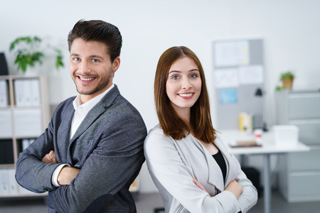 arms folded: two successful business colleagues standing together with arms folded