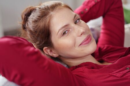 laid back: woman leaning back on her sofa while smiling at the camera