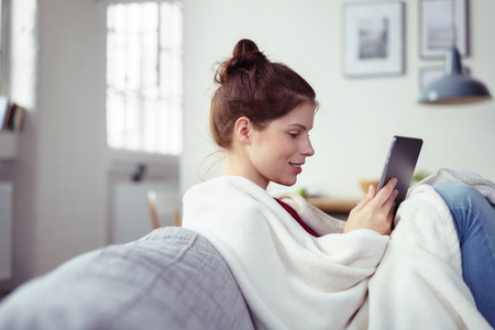 relaxing: Happy young woman enjoying an e-book on her tablet computer as she relaxes with her feet up on the couch wrapped in a warm blanket, side view with copyspace Stock Photo
