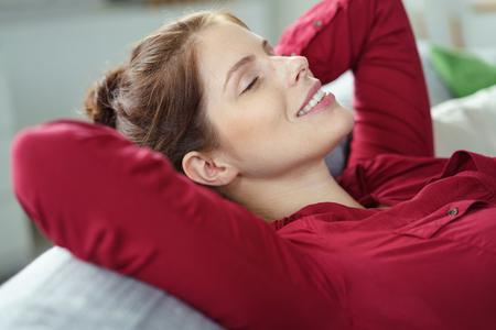 Blissful Frau auf einem Sofa zu Hause entspannen mit ihrem Kopf auf die gefalteten Hände liegend, die Augen geschlossen und ein schönes Lächeln der Freude, Nahansicht Standard-Bild