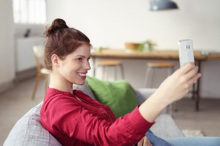 bollos: mujer sentada en el sofá sosteniendo su teléfono inteligente en la mano