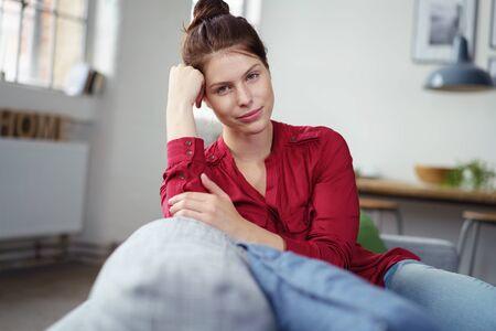 mujer pensativa: Mujer pensativa pensativo relajante en un sofá mirando fijamente a la cámara con la cabeza apoyada en la mano