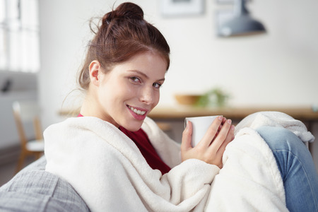woman wrapped in a blanket on the sofa holding a cup of warm tea in her hands smiling at the camera Imagens