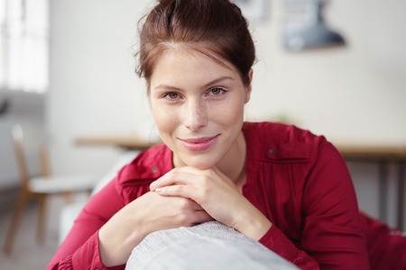 leans on hand: attractive young woman reclining with her head on her hands Stock Photo