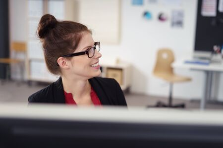specs: smiling businesswoman talking to someone at the office Stock Photo