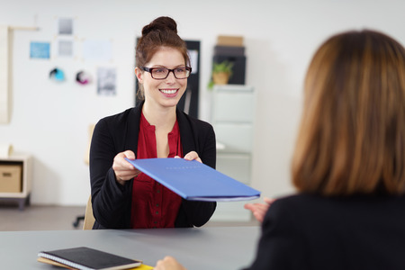 company job: Pretty young female job applicant handing over her CV to the personnel officer at the company with a friendly smile in an employment and human resources concept