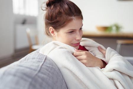 夢のような笑みを浮かべて彼女のソファに座って暖かい毛布に寄添う女性 写真素材