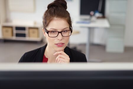 stylish businesswoman with her hair in a bun looking concentred on the computer