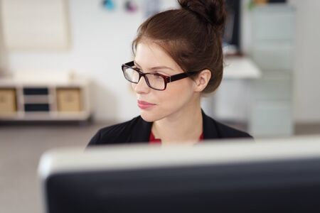preoccupied: thoughtful young businesswoman sitting in front of the computer looking to a side in thoughts Stock Photo