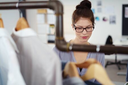choosing: young fashion designer looking at the dresses hanging in the studio Stock Photo