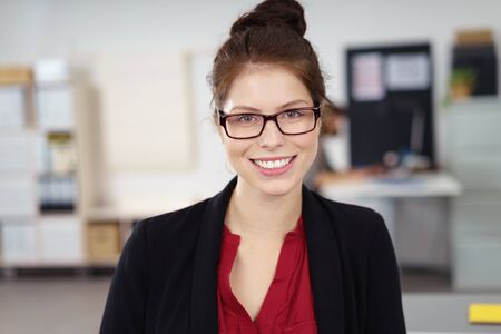 contented: Portrait of Young Brunette Businesswoman with Hair in Bun and Wearing Eyeglasses Smiling at Camera in Modern Office