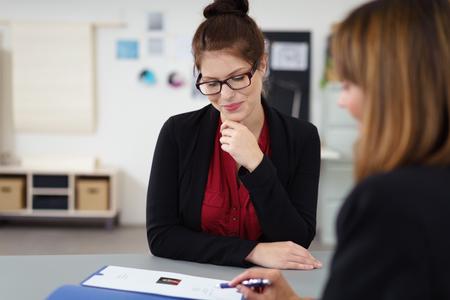 puesto de trabajo: dos mujeres en una entrevista de trabajo sentado en el escritorio mirando un currículum vitae Foto de archivo
