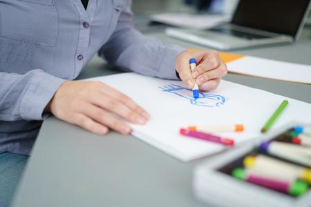 artistas: Artista Femenina dibujar algo en un Libro Blanco Utilizando crayones en su mesa. Foto de archivo