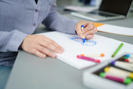 Female Artist Draw Something on a White Paper Using Crayons at her Table.