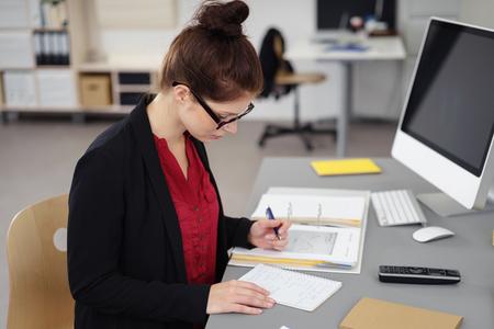 correspondence: ocupada joven empresaria dentro de un lugar de trabajo moderno escribiendo una lista de verificación