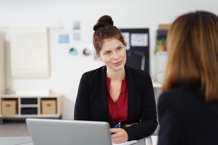 attentive young businesswoman listening to female colleague Фото со стока