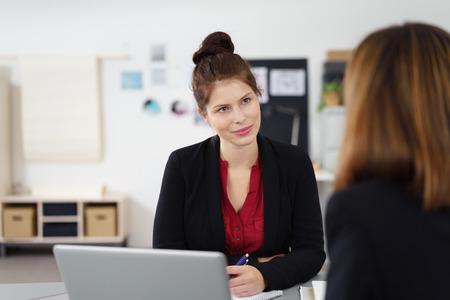 aufmerksam junge Unternehmerin zu weiblichen Kollegen hören