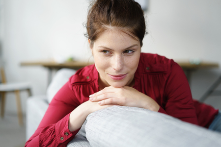 musing: Close up Thoughtful Pretty Woman Resting her Chin on her Hands While Sitting on the Couch in the Living Room.