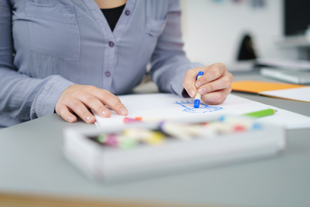 draftsman: Female Cartoonist Draw Something on a White Paper Using Crayons at the Table Inside the Office. Stock Photo