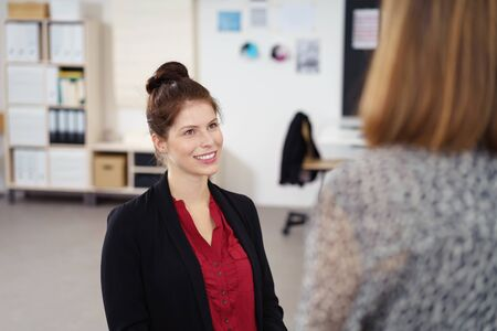colleagues: businesswoman talking to her colleague at the office with a friendly facial expression