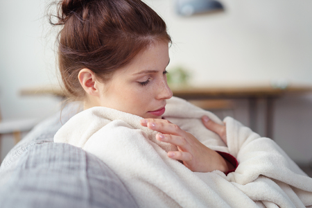 recuperating: woman with a cold wrapped in a blanket with eyes closed Stock Photo