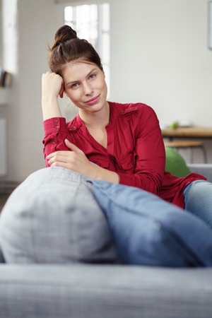contemplative: brunette woman sitting on her couch with a contemplative facial expression