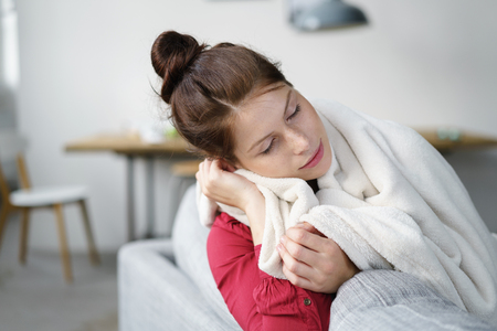 calm woman: Sick Young Woman Covered with Blanket Sitting at the Couch In the Living Room.