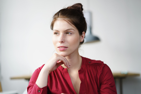 introspective: Portrait of a Pensive Young Woman with Hand on her Chin, Looking Into the Distance with Half Smile Face.