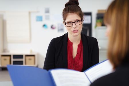 entrevista: Mujer joven con estilo con gafas sentado en una entrevista de trabajo esperando y observando el entrevistador de cerca mientras ella lee su curriculum vitae