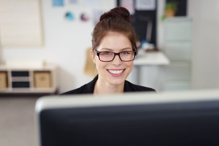 brunette businesswoman with black spectacles smiling over her screen