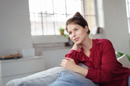 introvert: relaxing woman sitting on her sofa in a fabric style flat Stock Photo