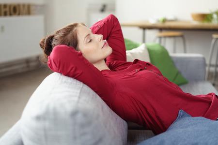 casalinga: Donna attraente che riposa su un divano a casa sdraiato contro i cuscini con le mani incrociate dietro la testa e gli occhi chiusi