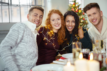 festooned: four friends sitting at the table celebrating christmas at home Stock Photo