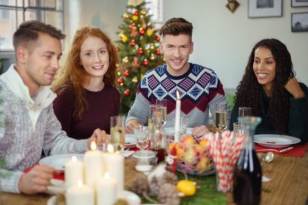cena navideña: cuatro adultos jóvenes que celebran la Navidad con una cena en casa Foto de archivo