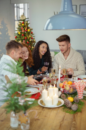 dinner party: four young adults celebrating christmas with a dinner at home