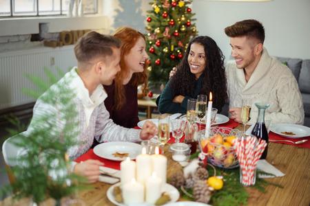 riendo: adultos j�venes que se sientan en una mesa festiva de la Navidad y la risa