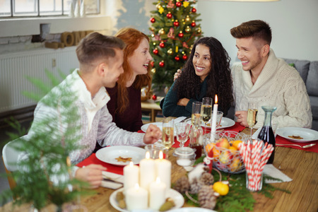 woman laughing: young adults sitting at a festive christmas table and laughing