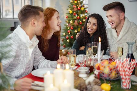 amici seduti intorno a un tavolo di legno e godersi la cena di Natale insieme