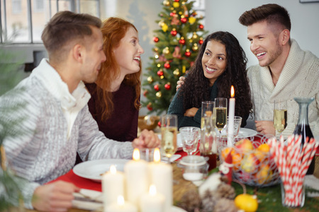 Freunde sitzen um einen Holztisch und gemeinsam genießen Weihnachtsessen Lizenzfreie Bilder
