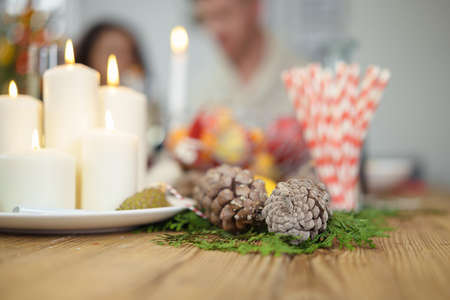setting: candles burning on a wooden table at christmas time