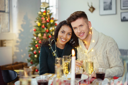 comida de navidad: feliz pareja que celebra la Navidad decorado con una cadena de luces