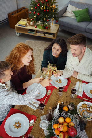 group of friends toasting with champagne while having choristers dinner Stock Photo