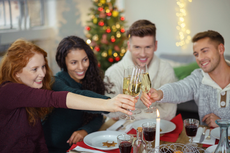decorated christmas tree: group of friends toasting with champagne while having christmas dinner