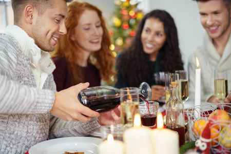 decorated christmas tree: man pouring wine to his friend´s glas while having christmas dinner Stock Photo