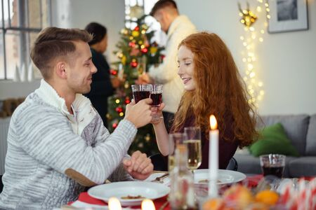 camaraderie: couple in love toasting with red wine while sitting around the table at christmas dinner Stock Photo
